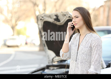 Serious driver with a broken down car calling insurance on phone on the street - Stock Photo