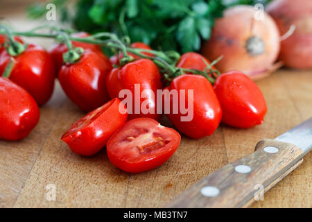 Grape tomatoes on vine with one halved tomato on wood chopping board next to a kitchen knife. - Stock Photo