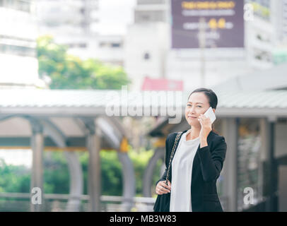 Portrait of cheerful young woman talking on smartphone and laughing outdoors. Happy beautiful caucasian business woman using mobile phone, making call - Stock Photo