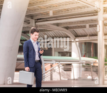 Man on smartphone.Portrait of a confident Asian businessman using phone walking in the city. - Stock Photo