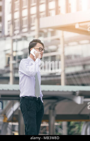 Portrait of serious man talking on smartphone outdoors. caucasian businessman using mobile phone, making call on the street in city. Copy space - Stock Photo