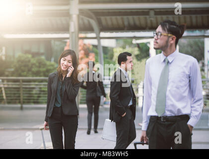 Candid of cheerful young woman talking on smartphone and laughing outdoors. Happy beautiful Asia business woman using mobile phone, making call on the - Stock Photo