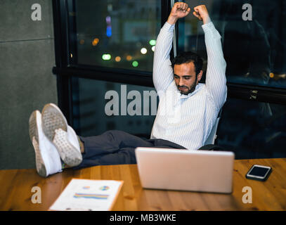 relaxed confident young businessman sitting with legs on desk at office work late overtime at night Table footrest - Stock Photo