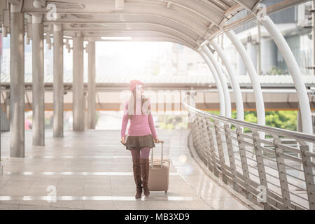 Portrait of a traveling young woman with luggage walking through the poles lined of international airport terminal - Stock Photo
