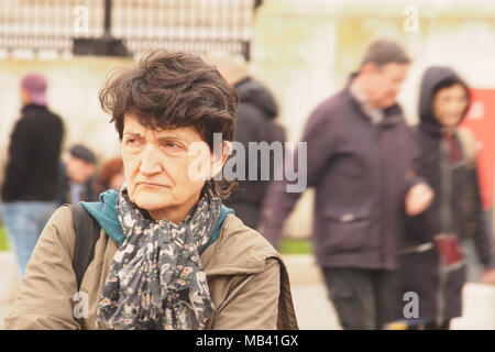 An older woman standing among pedestrians in London wrapped up in a thick coat and scarf looking miserable and fed up - Stock Photo