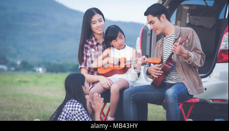 happy little girl playing ukulele with asian family sitting in the car for enjoying road trip and summer vacation - Stock Photo