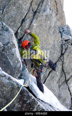 male mountain climber traverses a tricky rock chimney on his way to a high alpine summit - Stock Photo