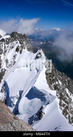 narrow and exposed summit ridge with a giant wave cornice on the way to the top of a peak in the Alps - Stock Photo