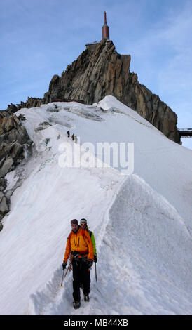 mountain guide and a male client on a rocky ridge heading towards a high summit in the French Alps near Chamonix - Stock Photo