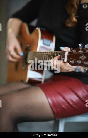 young girl in a red leather miniskirt and black pantyhose playing the guitar, close-up, shallow depth of field. - Stock Photo