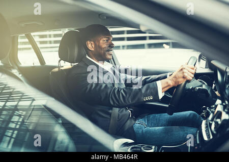 Young African businessman smiling while driving his car during his morning commute to work in the city - Stock Photo