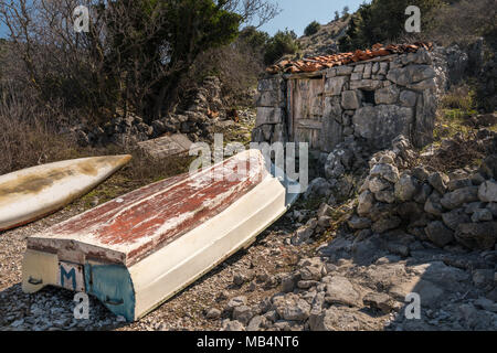 Boat lying in front of old stone house in a cove near Ustrine, Cres Croatia on a sunny day in spring - Stock Photo