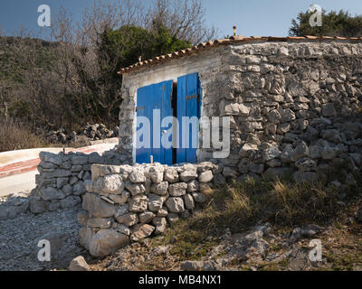 Old stone house with colorful blue doors in a cove near Ustrine, Cres Croatia - Stock Photo