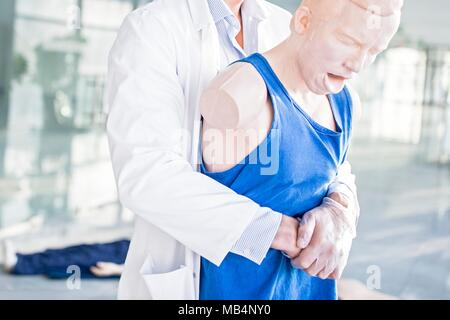 Doctor practising the Heimlich manoeuvre on a training dummy. - Stock Photo