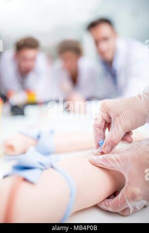 MODEL RELEASED. Doctor practising inserting an IV (intravenous) line on a training dummy. - Stock Photo