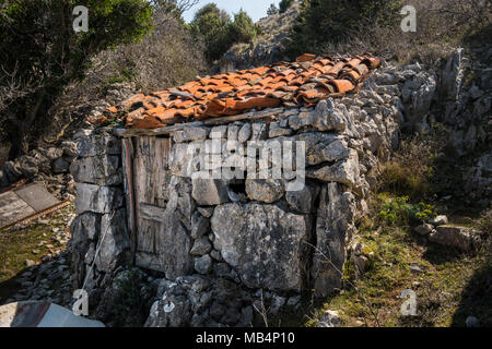 Old stone house with colorful roof in a cove near Ustrine, Cres Croatia - Stock Photo