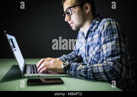 Young man working on computer at night in dark office. The designer works in the later time. A young man sits at the computer - Stock Photo