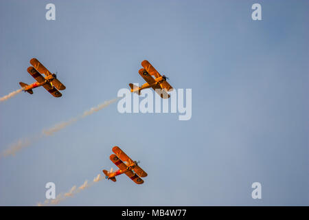 Three biplanes with exhaust trails against a blue sky. - Stock Photo