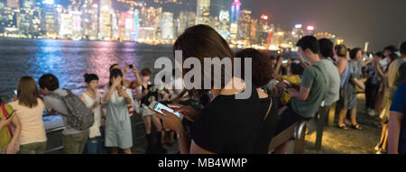 KOWLOON HONG KONG, SEPTEMBER 20, 2017; Tourists gather along Walk od Stars to view and take selfie of Victoria Harbor and comercial skyline at night. - Stock Photo