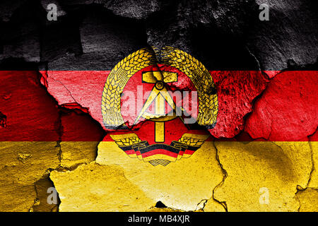 flag of East Germany painted on cracked wall - Stock Photo