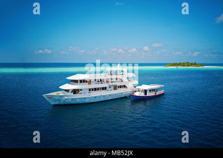 Diving safari ship MS Keana with diving dhoni anchored off an uninhabited palm island, Ari Atoll, Indian Ocean, Maldives - Stock Photo