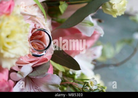 close up of two wedding rings on a white and pink bridal bouquet with subject on the left - Stock Photo