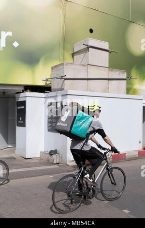 A Deliveroo rider cycles past large concrete blocks, part of a construction site on the corner of Brook and New Bond Streets, on 6th April 2018, in London, England. - Stock Photo