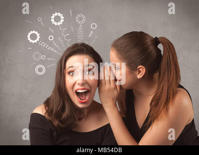 Two girlfriends in elegant black dress sharing secrets with each other concept with drawn rack cog wheels and spiral lines on the wall background. - Stock Photo