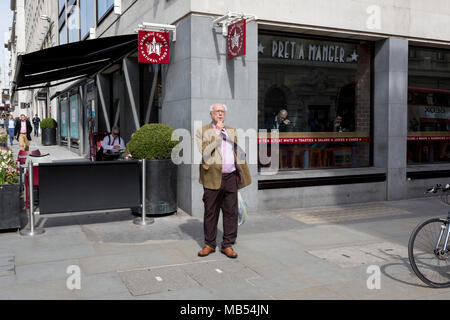 An elderly man vapes on the corner of a central London street, on 6th April 2018, in London, England. - Stock Photo
