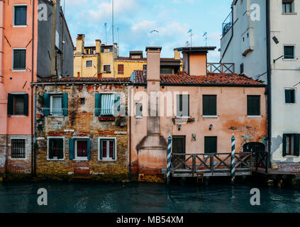 Facade of partially mossy old brick house with wooden vintage door on narrow canal in Venice, Italy - Stock Photo
