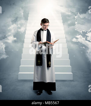 A young religious happy priest standing in front of the stairway to heaven concept with clouds and bright lights coming from above. - Stock Photo