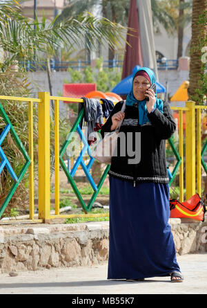 Aqaba, Jordan, March 7, 2018: Middle-aged Muslim woman standing on her mobile phone, laughing at the same time, midle east - Stock Photo