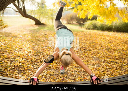 Young sportswoman stretching her legs at wooden bench in public park - Stock Photo