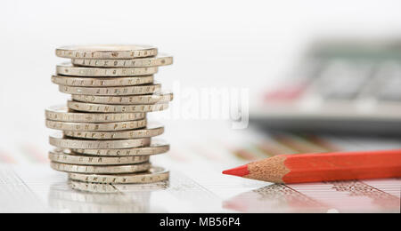 stacked euro coins and calculator laying on financial business chart - Stock Photo