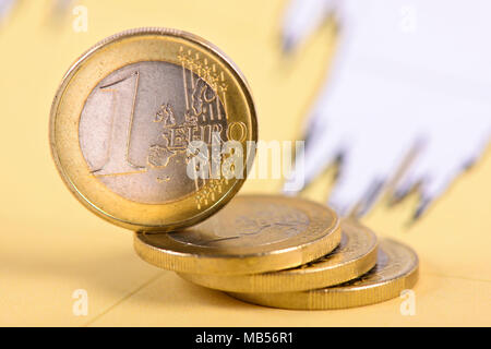 stacked euro coins laying on financial business chart - Stock Photo