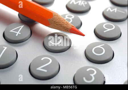 red pencil laying on top of calculator - Stock Photo
