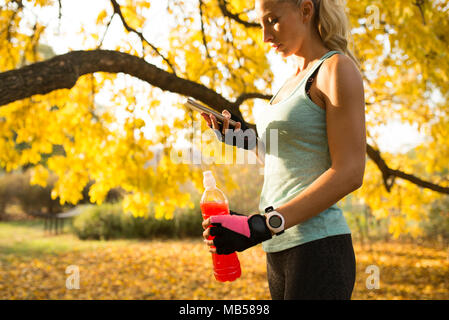 Attractive blonde sportswoman refreshing with cold drink and using her smart phone. Healthy lifestyle concept. - Stock Photo