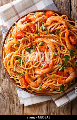 Italian pasta spaghetti with prawns, parmesan and herbs in tomato diavolo sauce close-up on a plate. Vertical top view from above - Stock Photo