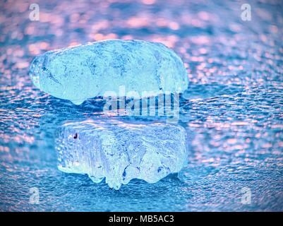 Shiny cold ice pieces on clear ice floe. Structure of natural ice in selective focus photograph.  Vivid colors of polar sunset. - Stock Photo