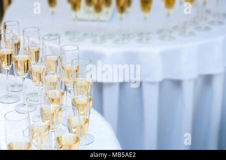 A lot of wine glasses with a champagne or white wine on the round table. Alcohol background - Stock Photo