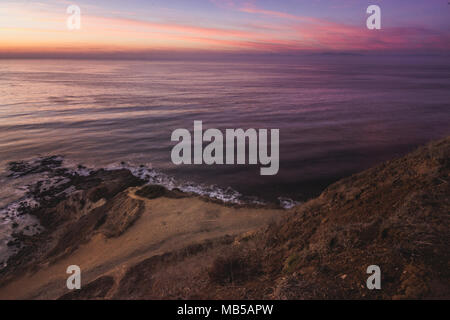 Long-exposure shot of smooth waves crashing into Flat Rock Point rock formations and Bluff Cove Trail after sunset, Palos Verdes Estates, California - Stock Photo