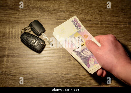 The concept of selling and buying a car. Car keys laid on the table. A hand holding Czech banknotes. Money to repair the car. Financial concept. - Stock Photo