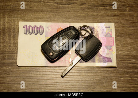 The concept of selling and buying a car. Car keys laid on Czech banknotes. Money to repair the car. Financial concept. - Stock Photo