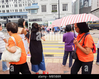 KOWLOON HONG KONG - SEPTEMBER 20, 2017; grainy candid close-up mobile phone image women at city pedestrian crossing one with striped umbrella - Stock Photo