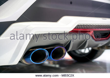 New generation of sportive mufflers. Oval Car Exhaust Tailpipe chromed made of stainless steel on powerful sport car bumper. Close up - Stock Photo