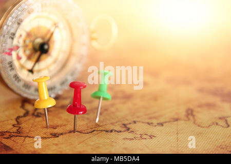 Image of pins attached to map, showing location or travel destination next to vintage compass. selective focus - Stock Photo