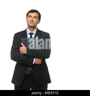 handsome young businessman in business sut, blue shirt and tie holding tablet in leather case. happy expression. man greeting someone. studio shot iso - Stock Photo
