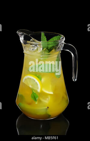 Cold Lemon and mint cocktail with a sparkling wine with ice cubes in pot isolated on black - Stock Photo