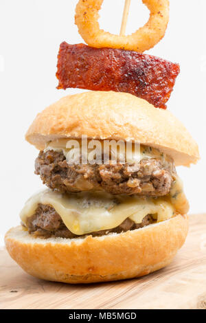 A double wild boar burger made from a boar shot in Tuscany Italy, featuring cambozola cheese and garnished with chorizo sausage and deep fried onion r - Stock Photo
