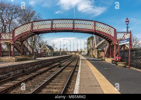 Looking down the salt gritted platform and railway tracks of Kirkby Stephen on a beautiful spring day, Yorkshire Dales - Stock Photo